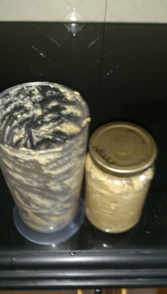 transferring peanut butter into glass jar for storage
